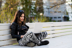 Retrato cercano del estudiante de mujer magnífico del oscuro-pelo que usa el ordenador portátil en el campus, adolescente femenin Foto de archivo libre de regalías
