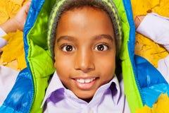 Retrato cercano del muchacho negro en hojas de otoño Imagenes de archivo