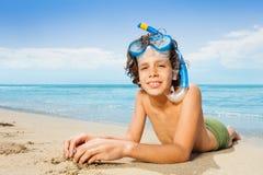 Retrato cercano del muchacho que pone en la playa de la arena Foto de archivo libre de regalías