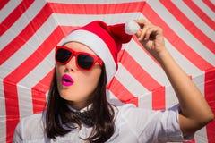 Retrato cercano para arriba de una mujer bastante joven en el sombrero de Santa Claus Imágenes de archivo libres de regalías