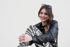 Retrato cercano y de una mujer hermosa joven que se sienta en banco al aire libre, sonriendo y mirando a la cámara Fotografía de archivo libre de regalías