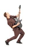 Retrato cheio do comprimento de uma estrela do rock que joga a guitarra Fotografia de Stock