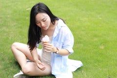 Retrato chino de la mujer feliz joven que come el helado Foto de archivo