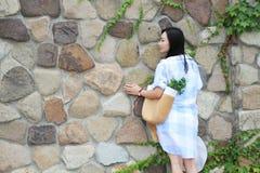Retrato chino de la mujer hermosa joven contra a la pared en parque Foto de archivo libre de regalías