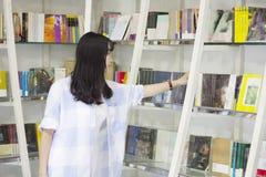 Retrato chino de la mujer hermosa joven que alcanza para un libro de la biblioteca en librería fotografía de archivo