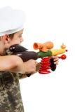 Retrato chistoso de un cocinero con el rifle de verduras En el fondo blanco Fotografía de archivo