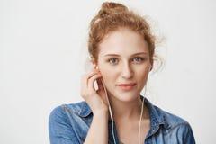 retrato Cierre-IP de la muchacha joven magnífica buena del pelirrojo con los ojos azules, los auriculares que llevan mientras que Imagenes de archivo