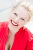 Jovem mulher de sorriso loura bonita no vermelho fotografia de stock