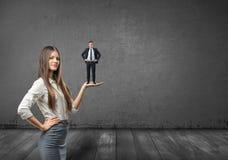 Retrato colhido da mulher de negócios grande que guarda o homem de negócios pequeno em sua palma Imagem de Stock