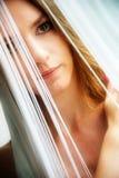 Retrato coloreado de una mujer atractiva joven, inclinado, que es obscurecida parcialmente por los hilos blancos de una cortina d fotos de archivo libres de regalías