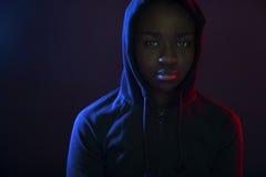 Retrato colorido de una mujer fresca con sudadera con capucha que lleva de la piel oscura Foto de archivo