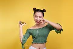 Retrato colorido del estudio de la mujer asiática joven feliz con el earphon Imagen de archivo