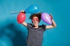 Retrato colorido del hombre divertido joven que presenta en la pared azul Fotografía de archivo