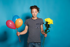 Retrato colorido del hombre divertido joven que presenta en la pared azul Imagen de archivo
