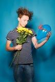 Retrato colorido del hombre divertido joven que presenta en la pared azul Foto de archivo libre de regalías