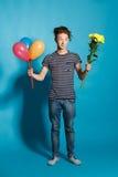 Retrato colorido del hombre divertido joven que presenta en la pared azul Fotografía de archivo libre de regalías