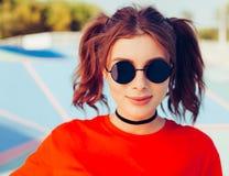 Retrato colorido del verano al aire libre de la mujer hermosa bastante joven en gafas de sol, divirtiéndose en el skatepark Imagenes de archivo