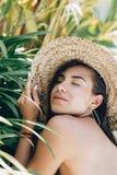 Retrato colorido del verano de las gafas de sol que llevan de la mujer morena atractiva joven debajo de una palmera por la piscin fotografía de archivo libre de regalías