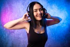 Retrato colorido no ligth azul e cor-de-rosa de uns auriculares vestindo e de apreciar da mulher nova do DJ uma música eletrônica imagem de stock