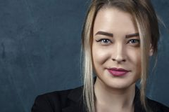 Retrato com lotes dos detalhes, mulher de sorriso bonita do close-up no terno preto contra um fundo estrutural azul da parede com Fotografia de Stock Royalty Free
