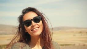 Retrato competido misturado de sorriso atrativo novo da menina em um deserto Mulher feliz do turista que levanta na câmera com o  filme