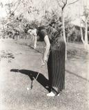 Retrato completo do comprimento da jovem mulher que joga o golfe no campo Foto de Stock Royalty Free