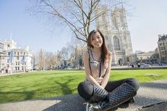 Retrato completo do comprimento da jovem mulher que senta-se contra a abadia de Westminster em Londres, Inglaterra, Reino Unido Fotografia de Stock Royalty Free