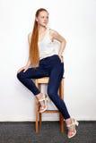 Retrato completo do comprimento da mulher bonita nova do modelo do novato do ruivo na calças de ganga branca do t-shirt que prati foto de stock