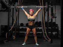 Retrato completo do comprimento da mulher muscular em um gym que faz exercícios pesados fotografia de stock