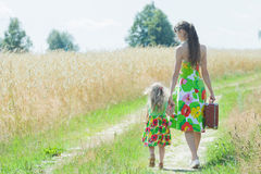 Retrato completo do comprimento da vista traseira da mãe de passeio e de sua filha pequena na estrada secundária rural imagem de stock royalty free