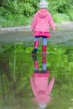 Retrato completo do comprimento da vista traseira da menina que veste os gumboots vermelhos que andam na poça grande da mola fotos de stock royalty free