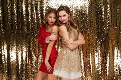 Retrato completo do comprimento de duas mulheres bonitas em vestidos sparkly Fotografia de Stock