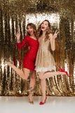 Retrato completo do comprimento de duas mulheres de sorriso em vestidos sparkly Fotos de Stock Royalty Free