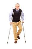 Retrato completo do comprimento de um cavalheiro feliz que anda com muletas Fotos de Stock Royalty Free