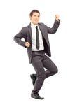 Retrato completo do comprimento de um homem de negócios novo feliz que gesticula o happ Fotos de Stock Royalty Free