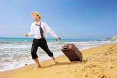 Retrato completo do comprimento de um homem de negócios perdido que leva uma mala de viagem a Fotografia de Stock Royalty Free
