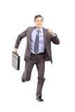Retrato completo do comprimento de um homem de negócios que corre com uma pasta a Fotos de Stock Royalty Free