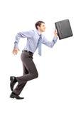 Retrato completo do comprimento de um homem de negócios que corre com uma pasta Imagens de Stock Royalty Free