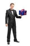 Retrato completo do comprimento de um homem elegante que guarda um presente Imagens de Stock Royalty Free