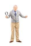 Retrato completo do comprimento de um homem maduro irritado que guardara uma correia Fotos de Stock Royalty Free