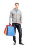 Retrato completo do comprimento de um homem ocasional novo que guardara sacos de compras Foto de Stock Royalty Free