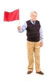 Retrato completo do comprimento de um homem superior triste que acena uma bandeira vermelha Fotos de Stock Royalty Free