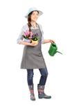 Retrato completo do comprimento de um jardineiro fêmea que guarda potenciômetros de flor Foto de Stock Royalty Free