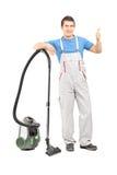 Retrato completo do comprimento de um líquido de limpeza masculino com um giv do aspirador de p30 Fotografia de Stock