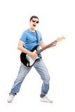 Retrato completo do comprimento de um músico masculino que joga um guit elétrico Imagens de Stock