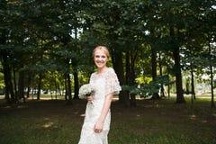 Retrato completo do comprimento de um par do recém-casado que guarda as mãos e que anda no parque Fotografia de Stock