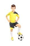 Retrato completo do comprimento de uma criança no sportswear que levanta com uma bola imagem de stock royalty free