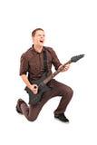 Retrato completo do comprimento de uma estrela do rock que joga uma guitarra Fotos de Stock Royalty Free