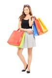 Retrato completo do comprimento de uma jovem mulher que levanta com sacos de compras Fotos de Stock Royalty Free