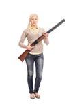 Retrato completo do comprimento de uma menina séria que guarda uma espingarda Fotografia de Stock